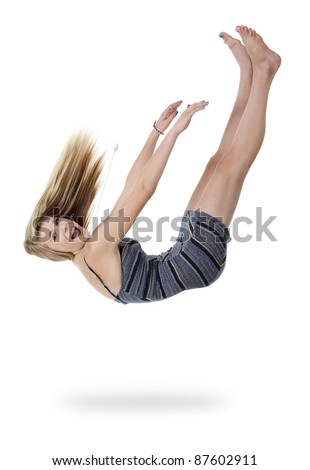 Pretty teenage girl upside down appears to be falling out of white space