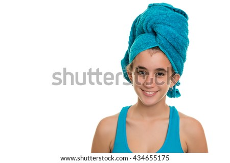 Pretty teenage girl with a blue towel wrapped over her wet hair  - Isolated on a white background - stock photo