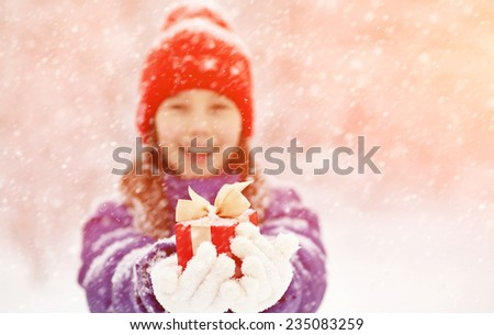 Pretty teenage girl with a gift in her hands. adolescent winter outdoors - stock photo