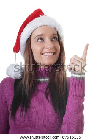Pretty Teenage Girl with a Santa Hat points upward - stock photo