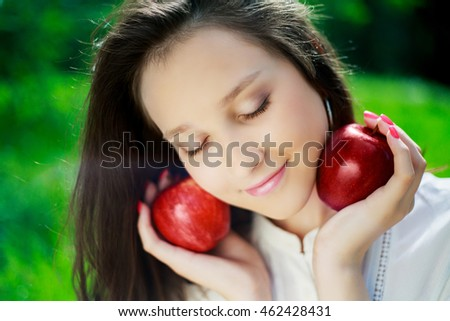 pretty teenage girl with apples outdoor on a summer day