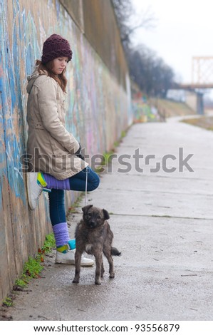 Pretty teenage girl with dog leaning against the wall on cloudy winter day. - stock photo