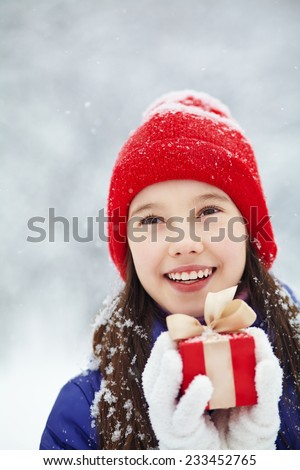 Pretty teenage girl with red gift in her hands. adolescent winter outdoors