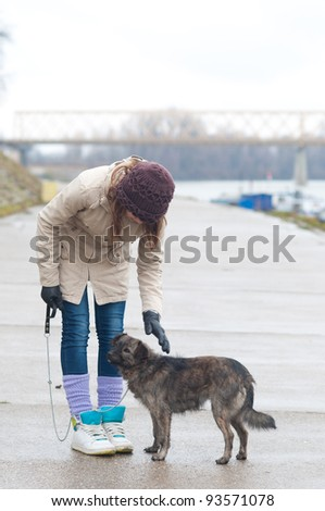Pretty teenage girl with the dog on cloudy autumn day. - stock photo