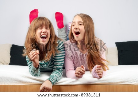 Pretty teenage girls singing while lying in bed. - stock photo