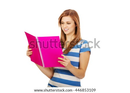 Pretty teenage woman reading her notes - stock photo