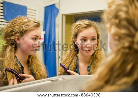 pretty teenager combing her hair in front of a mirror - stock photo