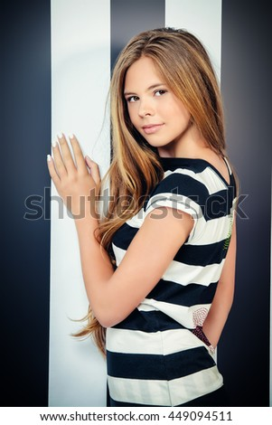 Pretty teenager girl posing in clothes in black and white stripes on the background of the same color. Modern style, youth fashion.
