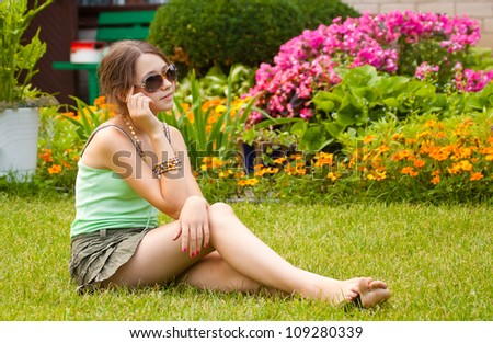 Pretty teenager girl sitting on the grass in the garden, with sunglasses - stock photo