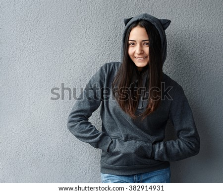 Pretty teenager girl smiling in a hoodie - stock photo
