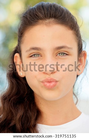 Pretty teenager girl with blue eyes throwing a kiss - stock photo