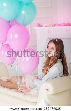 Pretty teenager girl with many blue and pink balloons - stock photo