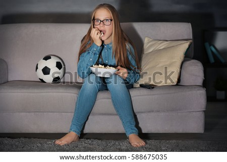 Pretty teenager watching football match late in evening