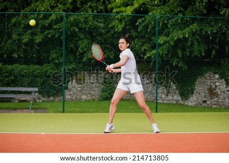Pretty tennis player about to hit ball on a sunny day