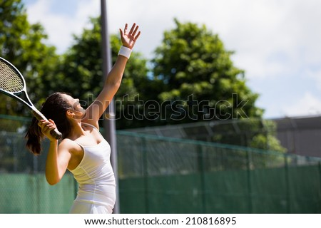 Pretty tennis player about to serve on a sunny day - stock photo