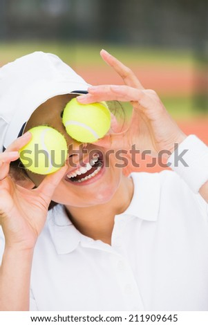 Pretty tennis player holding balls over her eyes on a sunny day - stock photo