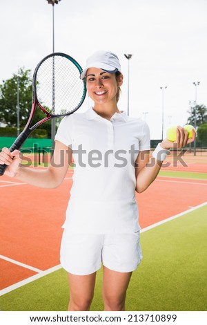Pretty tennis player smiling at camera on a sunny day - stock photo
