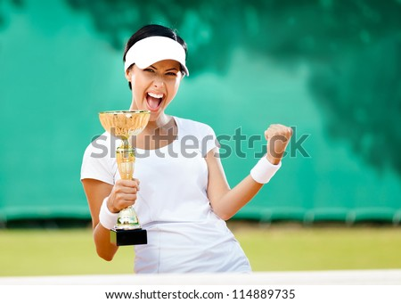 Pretty tennis player won the cup at the sport competition. Victory - stock photo