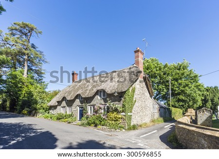 Pretty thatched stone cottage in Evershot, a small village in Dorset, southern England, in summer with blue sky - stock photo