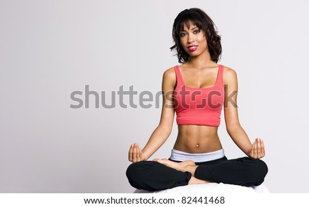 Pretty thin petite woman seated in lotus meditation doing yoga - stock photo