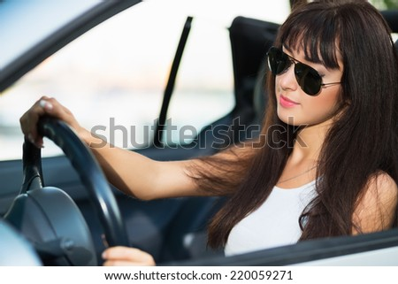 Pretty thoughtful brunette wearing sunglasses posing in grey car - stock photo