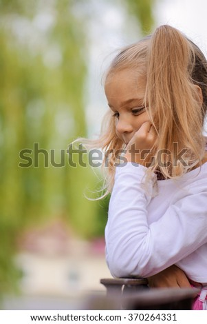 Pretty thoughtful little girl in a pink dress on a background of green summer city park. - stock photo