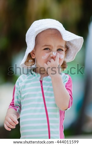 Pretty toddler girl in spf solar suit and hat applying sunscreen on her face at the beach. Safety in summer sun. - stock photo