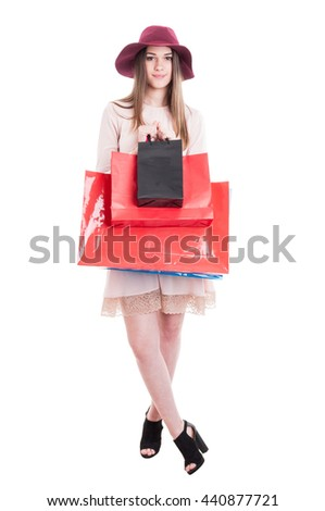 Pretty trendy woman in modern casual clothes showing black and red shopping bags isolated on white with advertising area - stock photo