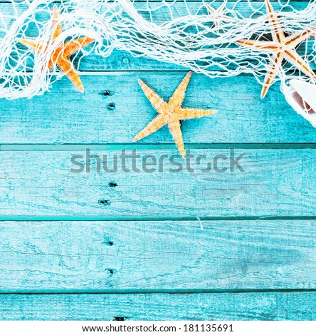 Pretty turquoise blue nautical background decorated with draped fishing net and starfish on painted rustic wooden boards with copyspace suitable as a card or party invitation, square format - stock photo