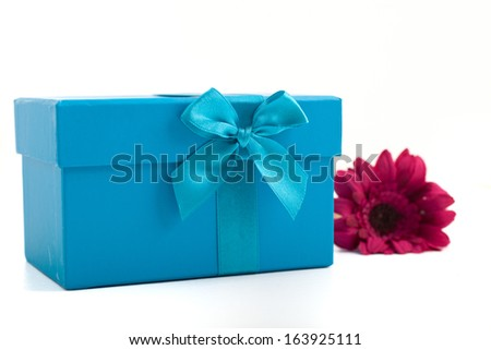 Pretty turquoise gift box tied with a decorative bow with a fresh purple Gerbera daisy alongside on a white background to give to a loved one on Christmas, a birthday or anniversary - stock photo