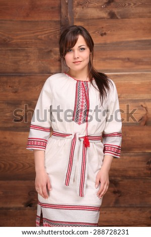 Pretty Ukrainian girl dressed in traditional costume embellished with embroideries. Woman with dark thick hair isolated on wooden background. - stock photo