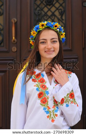 Pretty ukrainian girl stands and looking at camera. She is wearing national clothes with poppy flowers and flower crown. - stock photo