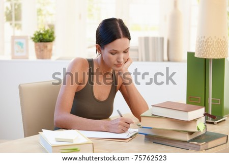 Pretty university student girl studying at home, sitting at desk, writing notes. - stock photo