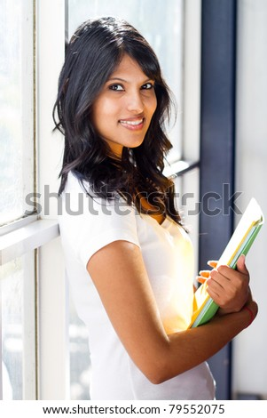 pretty university student standing by glass window - stock photo