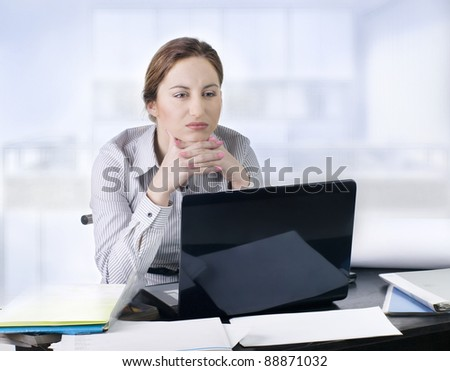 Pretty upset woman looking at a computer screen while sitting at the office