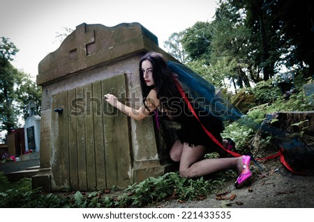 Pretty vampire open crypt and looking at camera - stock photo