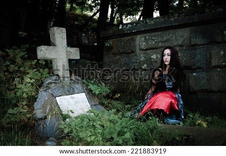Pretty vampire sits  near grave and looking to concrete cross - stock photo
