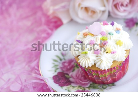 Pretty vanilla cupcake with sprinkles and pink candy heart, with pink background  copy space - stock photo
