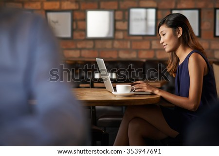 Pretty Vietnamese business lady computing and drinking cappuccino in cafe