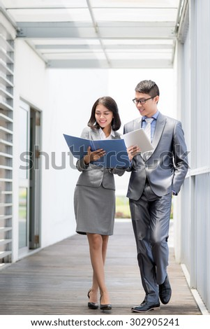Pretty Vietnamese business lady discussing document with her colleague