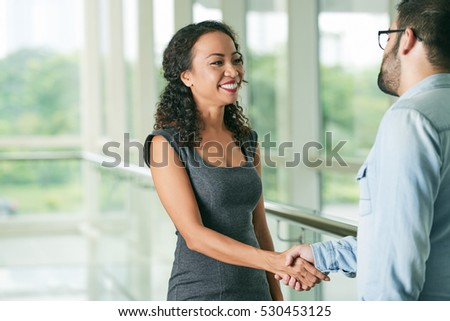 Pretty Vietnamese business lady shaking hand of her coworker