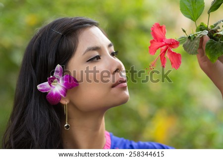 Pretty Vietnamese girl with a flower in her hair taking a close look at a tropical red hibiscus on the tree, side view with a serious expression against greenery - stock photo