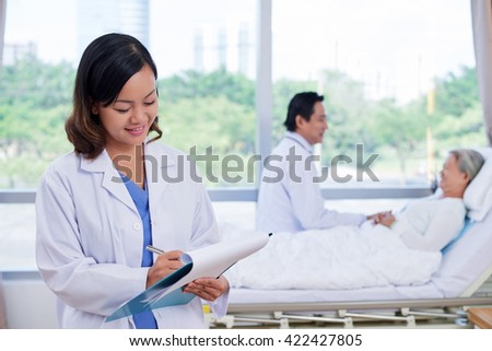 Pretty Vietnamese nurse whiting out prescription when doctor talking to patient