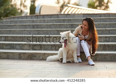 Pretty Vietnamese woman playing with her dog outdoors - stock photo