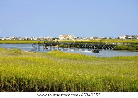 Pretty view of pristine Marshland with oceanfront development in background - stock photo
