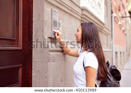Pretty visiting girl with a back pack buzzing the intercom at a wooden door wearing her hair loose, casual clothing - stock photo