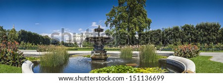 Pretty Volksgarten park with view of the Burgtheater (1888) in the background, lilly pads, flowers and lush summer vegetation in the foreground, Vienna, Austria. - stock photo