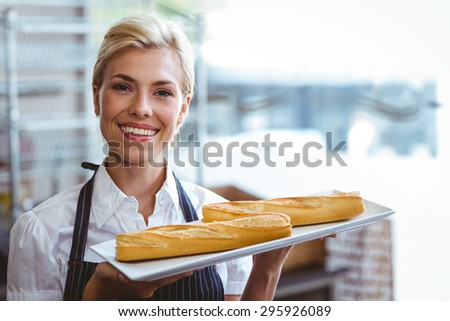 Pretty waitress carrying baguettes at the bakery - stock photo