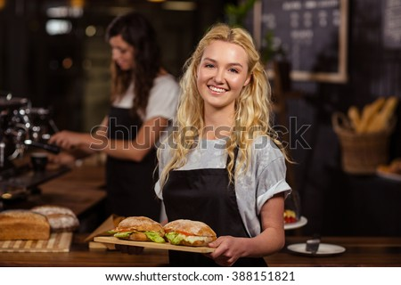 Pretty waitress holding a tray with sandwiches at the coffee shop - stock photo