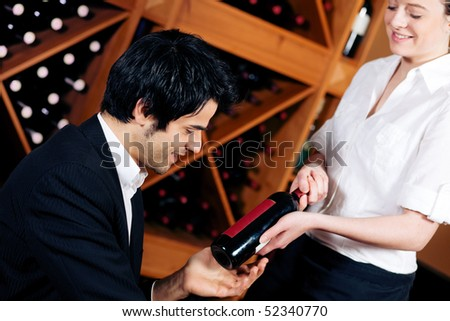 Pretty waitress in a wine bar offers a bottle of red wine to taste it a young Mediterranean looking man. - stock photo